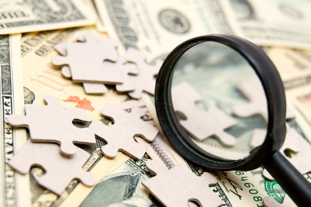 enlarger: Puzzle and magnifier on money (dollars). Stock Photo