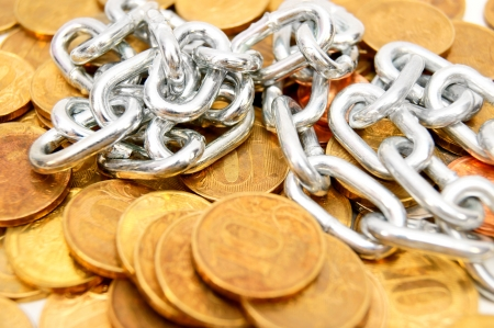 Iron chain against a scattering of gold coins. Stock Photo - 17237002