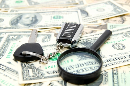 enlarger: Key from the car, a magnifier on dollars. Stock Photo
