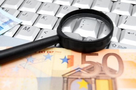 Magnifier and banknotes (euro) on the keyboard. photo