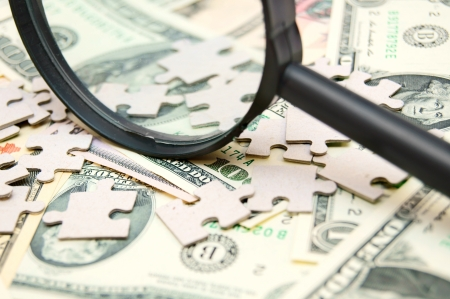 Magnifier and puzzles on dollars. Stock Photo - 17234524