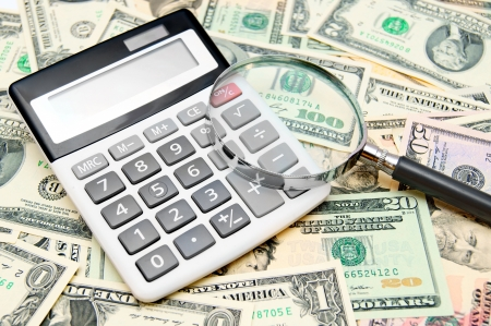 Calculator and magnifier on banknotes (dollars). Stock Photo - 17237109