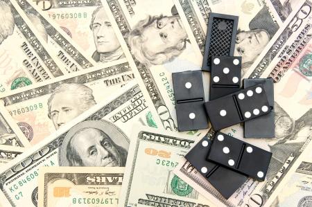 Dominoes on money (dollars). Stock Photo - 17237124