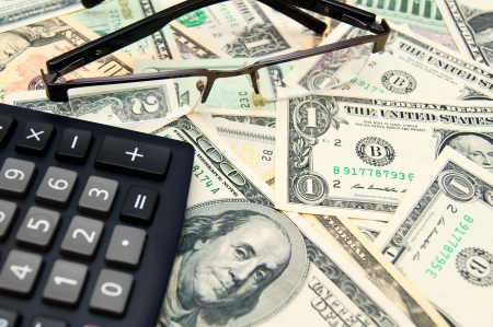 Glasses and the calculator on banknotes  dollars Stock Photo - 17237078