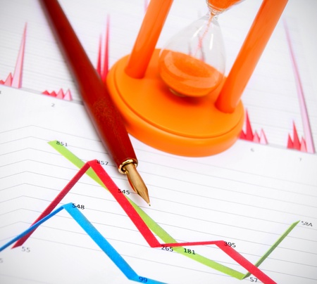 Pen and a sand-glass on graphs  Stock Photo