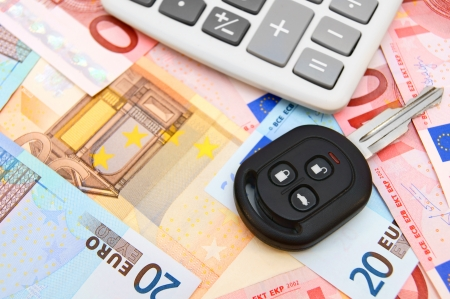 Keys from the car and the calculator on money. Stock Photo - 17237027