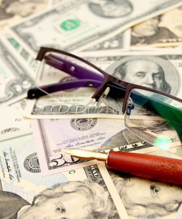 Glasses and pen on money. photo