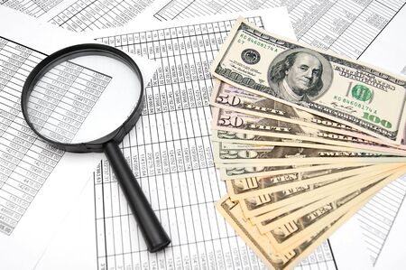 Magnifier and dollars on documents. Stock Photo - 17237087