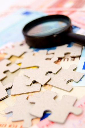 Puzzle and magnifier on documents. Stock Photo - 17224064