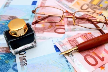 Glasses, pen, ink on money  Stock Photo