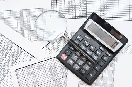 The calculator and magnifier on documents. Stock Photo - 17237091