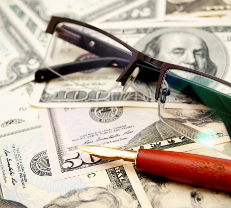 Glasses and pen on money  Stock Photo
