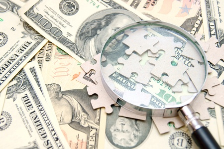 Magnifier and puzzle on money Stock Photo - 17224691