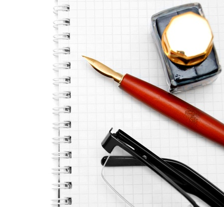 Glasses, pen and ink on a notebook Stock Photo - 17217512