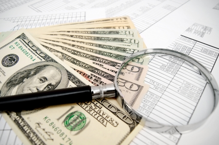 Magnifier and dollars on documents