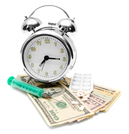 Tablets, a syringe and an alarm clock on money Stock Photo - 17217439