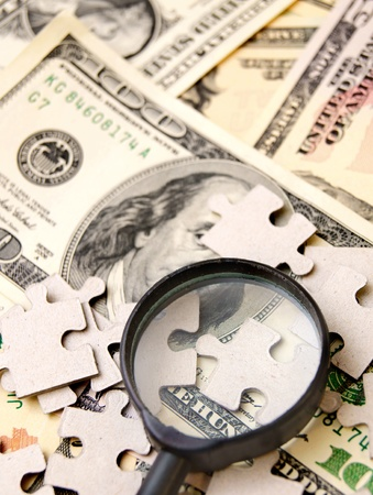 enlarger: Magnifier and puzzle on dollars  Stock Photo