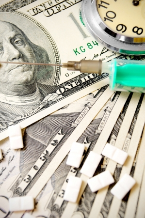 Hours, tablets and a syringe on dollars  Stock Photo