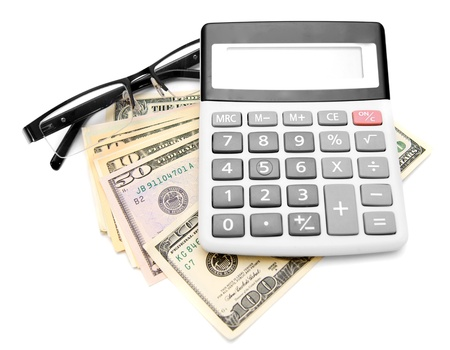 Calculator and glasses on a pack of dollars  Stock Photo