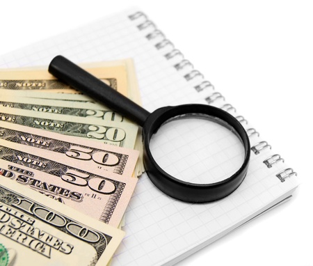 Magnifier and dollars on a notebook Stock Photo - 17217562