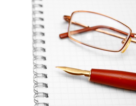 Pen and glasses on a notebook  Stock Photo - 17217456