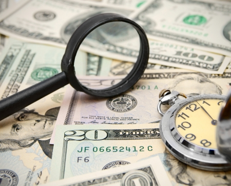 Magnifier and watches on dollars