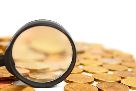 Magnifier and coins  On a white background Stock Photo - 17217486