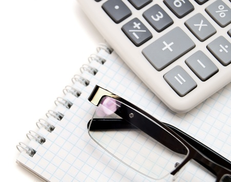 Glasses and the calculator on a notebook Stock Photo - 17217534