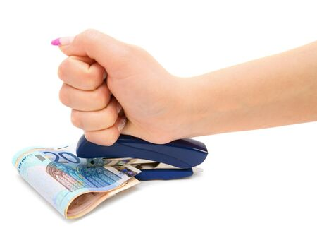 Stapler, money and a hand  On a white background  photo