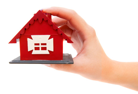 Toy small house in a hand at the girl. On the white. Stock Photo - 22244106