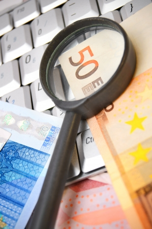 Magnifiers and euro on the keyboard. Stock Photo