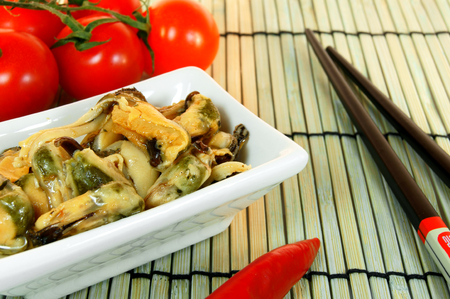 Tomatoes, mussels, pepper and chopsticks. photo