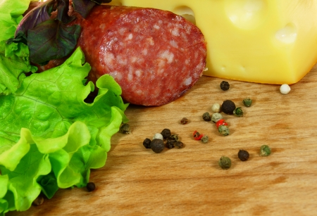 Sausage, cheese, greens, spices and basil on wooden board. photo