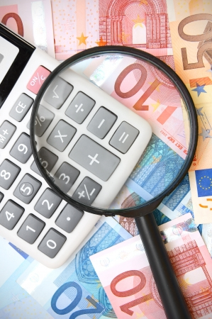 Magnifier and the calculator on money. Stock Photo