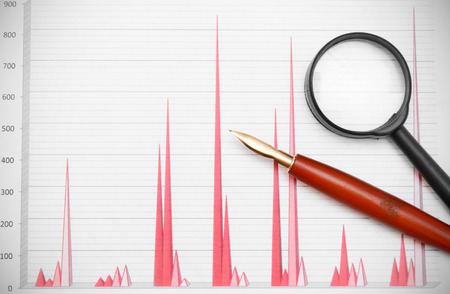 Magnifier and pen on financial graphs.