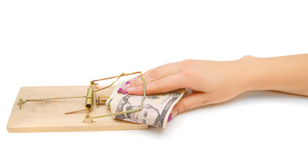Money in a mousetrap with a hand. On a white background. photo