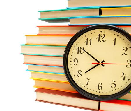 시계 및 흰색 배경에 많은 멀티 채색 된 책.