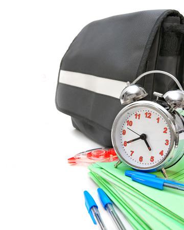 A portfolio, an alarm clock and school accessories. photo