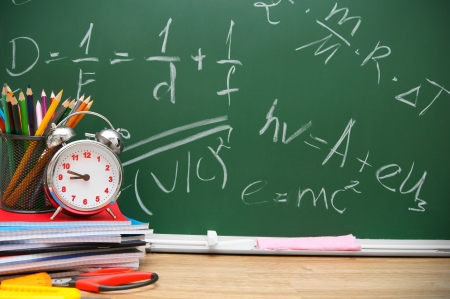 Alarm clock and stationery against a school board