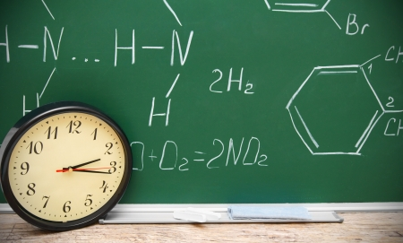 Watch against a school board with chemical formulas. photo
