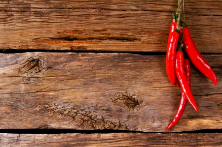 Red pepper on a cord. On a wooden background.