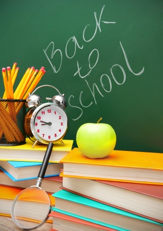 An alarm clock, an apple and school accessories photo