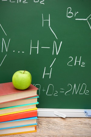 Apple and books against a school board (chemical formulas). photo