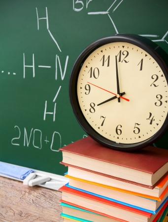 Watch and books against a school board (chemical formulas). photo