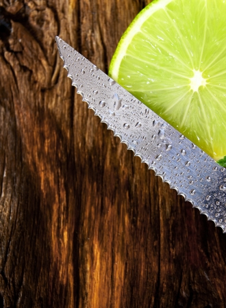 Lime and knife. On a wooden board. photo