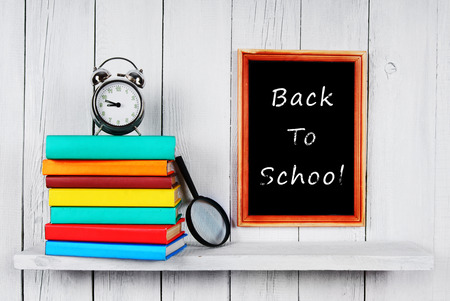 Back to school. Books and an alarm clock on a wooden shelf. A white, wooden background. photo