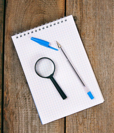 Notebook, pen and a magnifier on a wooden background. photo
