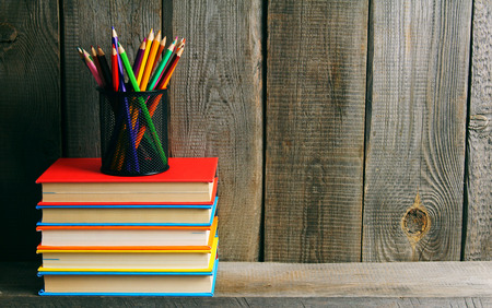 Books and pencils on a wooden shelf. On a wooden background. photo