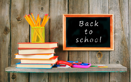 Back to school. Books and school tools on a wooden shelf. photo