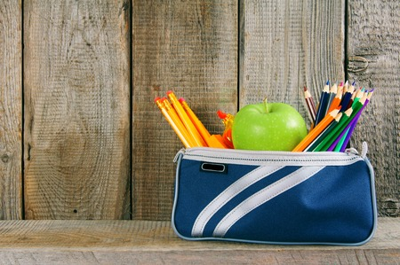 School tools in a case. On a wooden background. photo